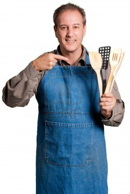 5771614-man-with-an-apron-showing-cooking-tools-against-a-white-background